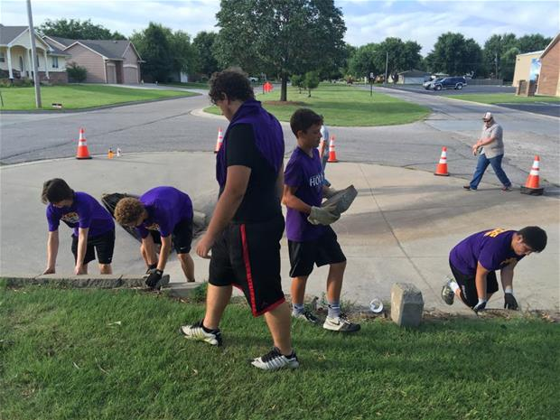 Picture of VCHS football team remove bricks for 3rd and Emporia sidewalk progress.